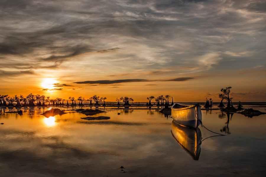 wooden boat on water under golden sky