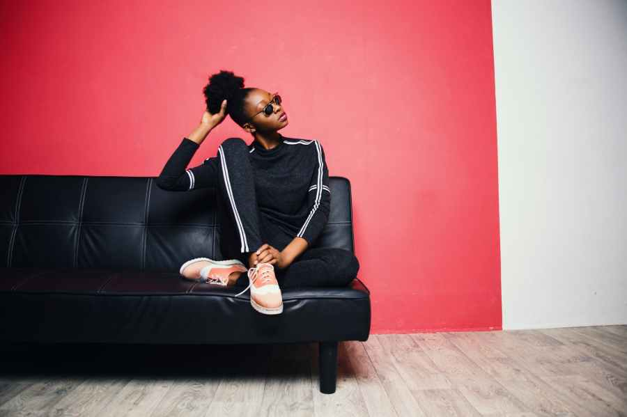 woman with black and white sweater with pants sitting on black leather sofa beside red painted wall