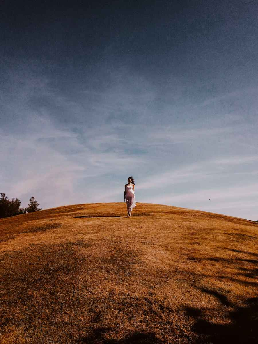 photo of woman standing on grass hill