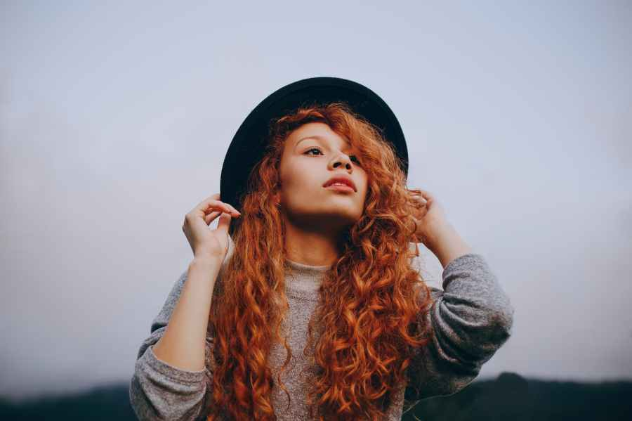 red haired woman wearing black round hat