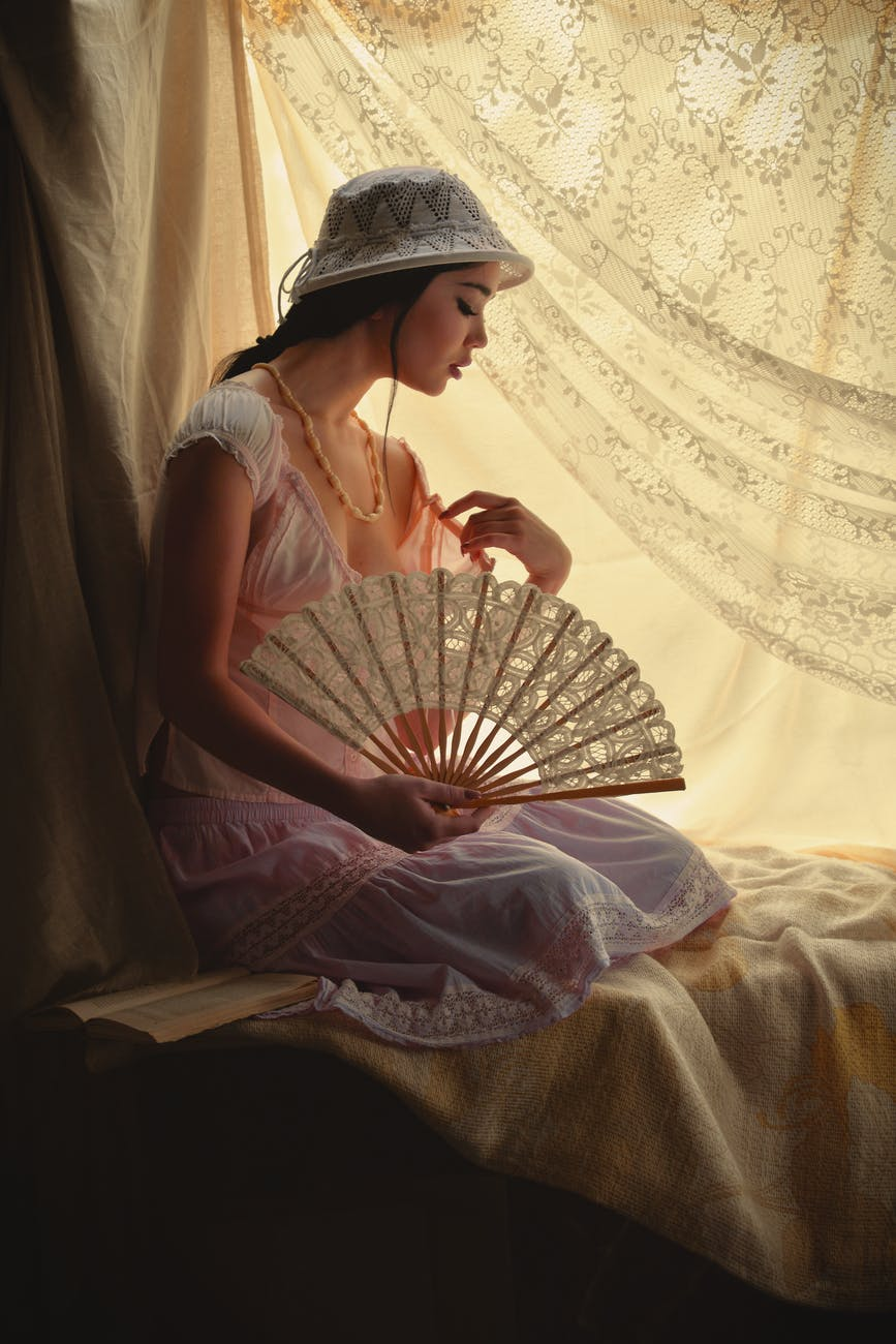 photo of woman sitting while holding her fan